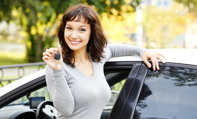 smiling woman holding keys to car